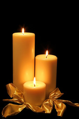 Three Christmas candles glow in the darkness.