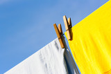 Linen and two clothes-pegs against the blue sky poster