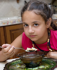 Dissatisfied girl eating soup