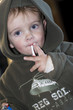Young boy smoking a cigarette sweet