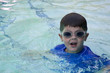 Cute boy swimming in pool wearing blue shirt and goggles