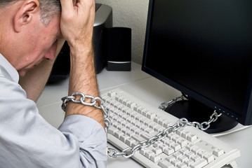 A man feeling as if he is chained to his computer