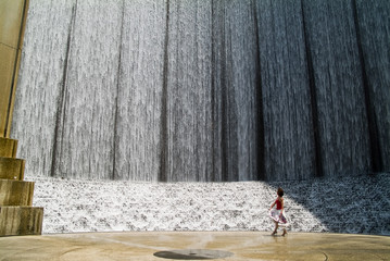 A woman playing in the moist breeze of a waterfall