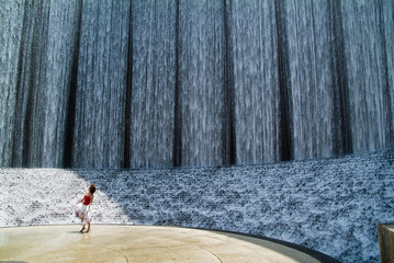 A woman miniaturized by a remarkable manmade waterfall.