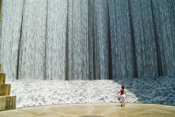 A woman dwarfed with a remarkable manmade waterfall.