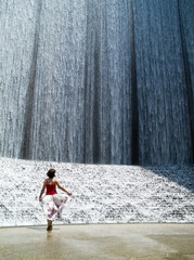 A woman enjoying with the splendor of a remarkable  waterfall
