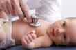 Close-up, high-key photo of a newborn baby getting examined