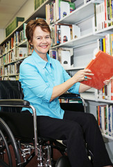 A pretty librarian in her wheelchair shelving books.