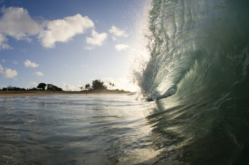 giant wave breaking in shallow water of sandy beach hawaii