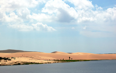 a beautiful landscape of sand dunes, lakes and clouds