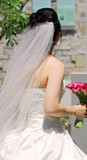 Young bride in veil and wedding gown carrying a bouquet poster