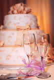 Three tiered wedding cake and champagne glasses on a table poster