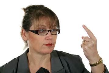 Mature businesswoman gesticulates to the assembled.