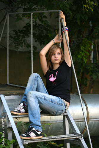 Teenage girl siiting against wall in a depressed state