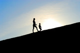 Silhouette of two girls walking up the hill