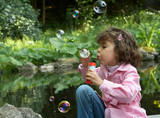 Little girl at the park pond blowing soap bubbles