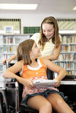 Two school girls in the library - one is in a wheelchair. poster