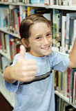 adorable school boy at the library giving a thumbs-up.   poster
