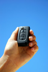 A hand showing a closed key of a Peugeot.