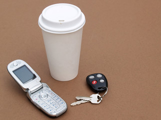to-go coffee cup, mobile phone and car keys