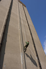 A person abseiling down a tall building