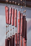 bamboo wind chimes hanging from roof in garden poster