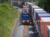 Locomotive pulling short train beside parked container cars poster