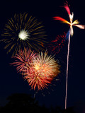 Cluster of fireworks bursts and a pinwheel poster