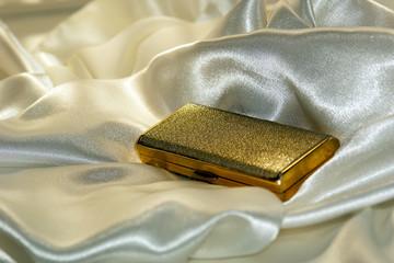 Gold cigarette case on soft white satin