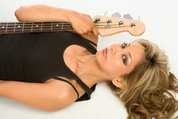 Beautiful Girl laying on the floor with bass guitar