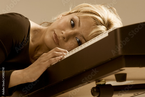blonde attractive Latina woman dreaming on piano
