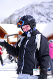 Young girl in ski gear holding a snowball at a skiing resort poster