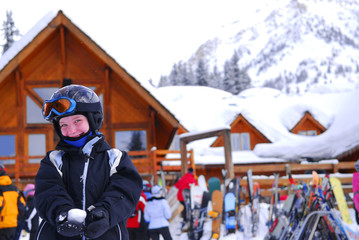 Young girl in ski gear holding a snowball at a skiing resort