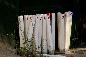 Poteaux blancs numérotés devant un mur sombre