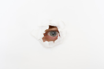 eye in the hole of white paper