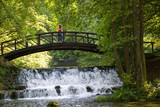 Fototapety young couple crossing over wooden bridge and small waterfall
