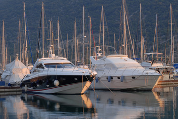 Yachts and motor boats in marina at sunset.