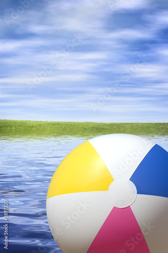 Leinwanddruck Bild beach ball river background, focus point on the toy
