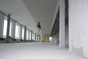 Arbeiter auf einer Baustelle sitzt auf einer Leiter