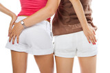 two lesbian women touch ass in short over white poster
