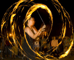 A woman dancing whit fire surrounded by people.