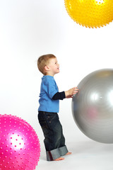 Little boy playing with big color balls