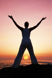 Woman in meditation pose at sunset with falling sun