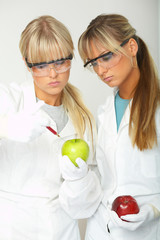 Female scientists injecting liquid into a apple