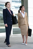 Two attractive business woman leaving their company poster