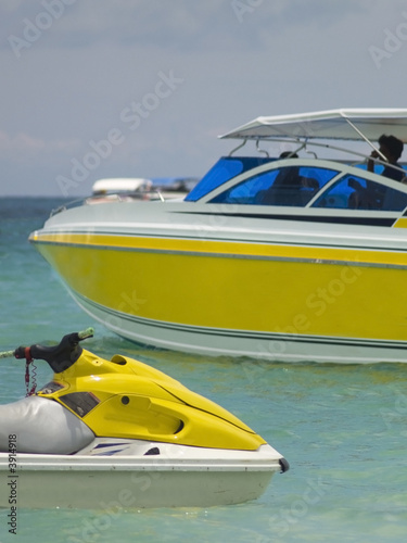 Yellow water scooter and speedboat at sea.