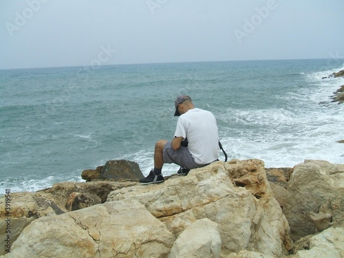 A man sitting alone on the rocks