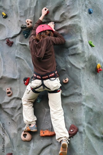 Young girl climbing to the rock climbing wall
