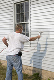 Contractor spray painting exterior of house poster