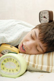 Pretty sleeping boy and his three alarm-clocks poster